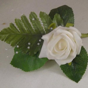 an artificial buttonhole featuring a foam rose with pearl strands and foliage