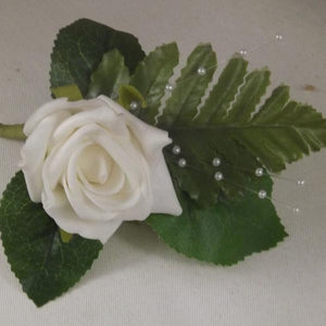 artificial wedding buttonhole featuring a single ivory rose