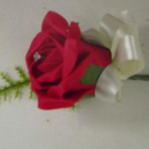 artificial buttonhole features a single red rose, ribbon bow,asparagus fern