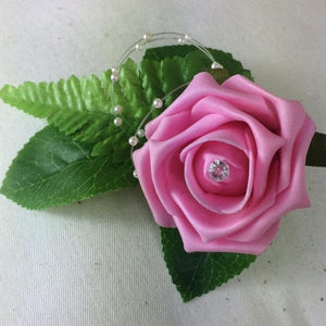 artificial wedding buttonhole of a pink foam rose, fern and pearl loops