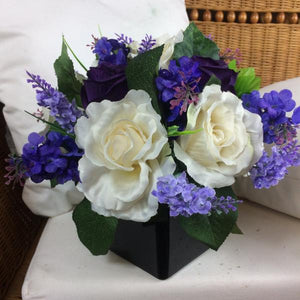 a table arrangement of lilac ivory and purple flowers