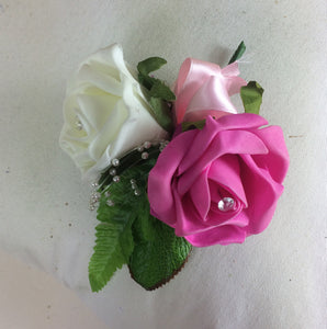 artificial wedding corsage features roses in shades of ivory and cerise