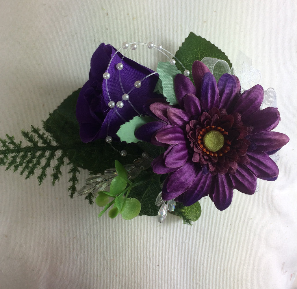 an artificial flower corsage of a purple rose and gerbera