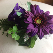 an artificial wedding corsage featuring a purple rose and gerbera with foliage