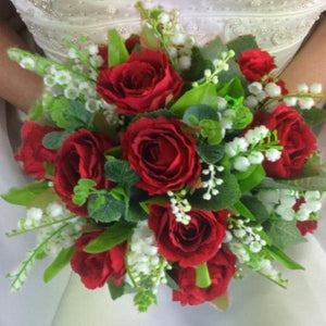 a wedding bouquet of red silk roses and white lily of the valley