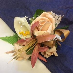 An artificial corsage of foam roses and calla lily