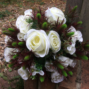 a wedding bouquet of burgundy thistles and ivory roses