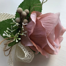 A wrist corsage featuring a mocha pink artificial silk rose