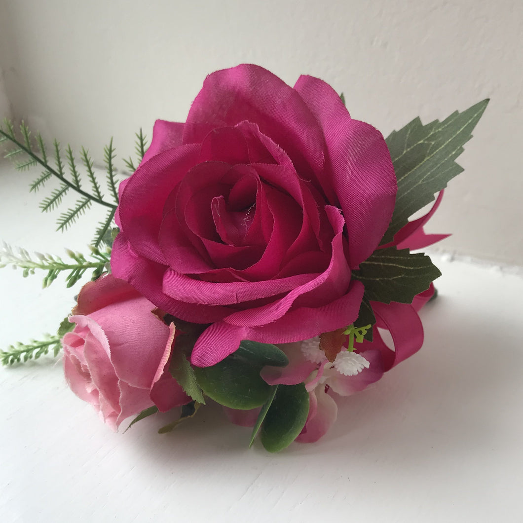 a cerise artificial rose corsage