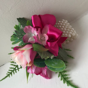 wrist corsage of cerise flowers