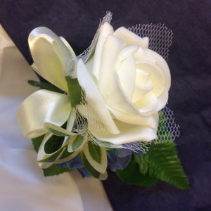 a buttonhole of ivory foam rose with netting