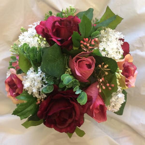 a brides bouquet of burgundy and pink roses
