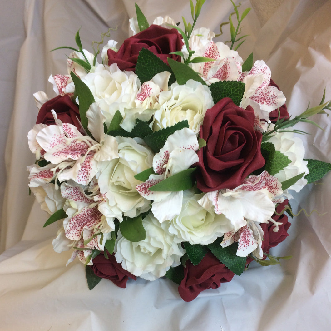 A WEDDING BOUQUET OF BURGUNDY AND IVORY ROSES