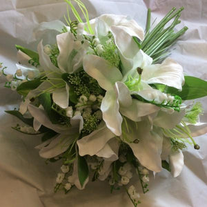 a wedding bouquet of artificial lilies and lily of the valley flowers