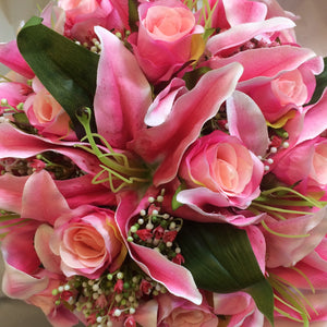 A wedding bouquet of artificial silk roses and lily flowers