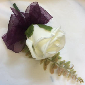 as artificial buttonhole featuring a single ivory rose & aubergine ribbon