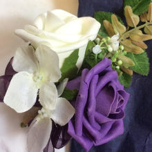 An artificial corsage featuring an ivory & aubergine foam rose