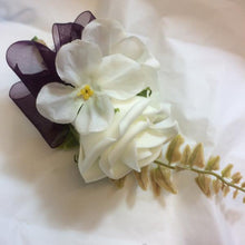A buttonhole featuring an ivory foam rose with hydrangea florets