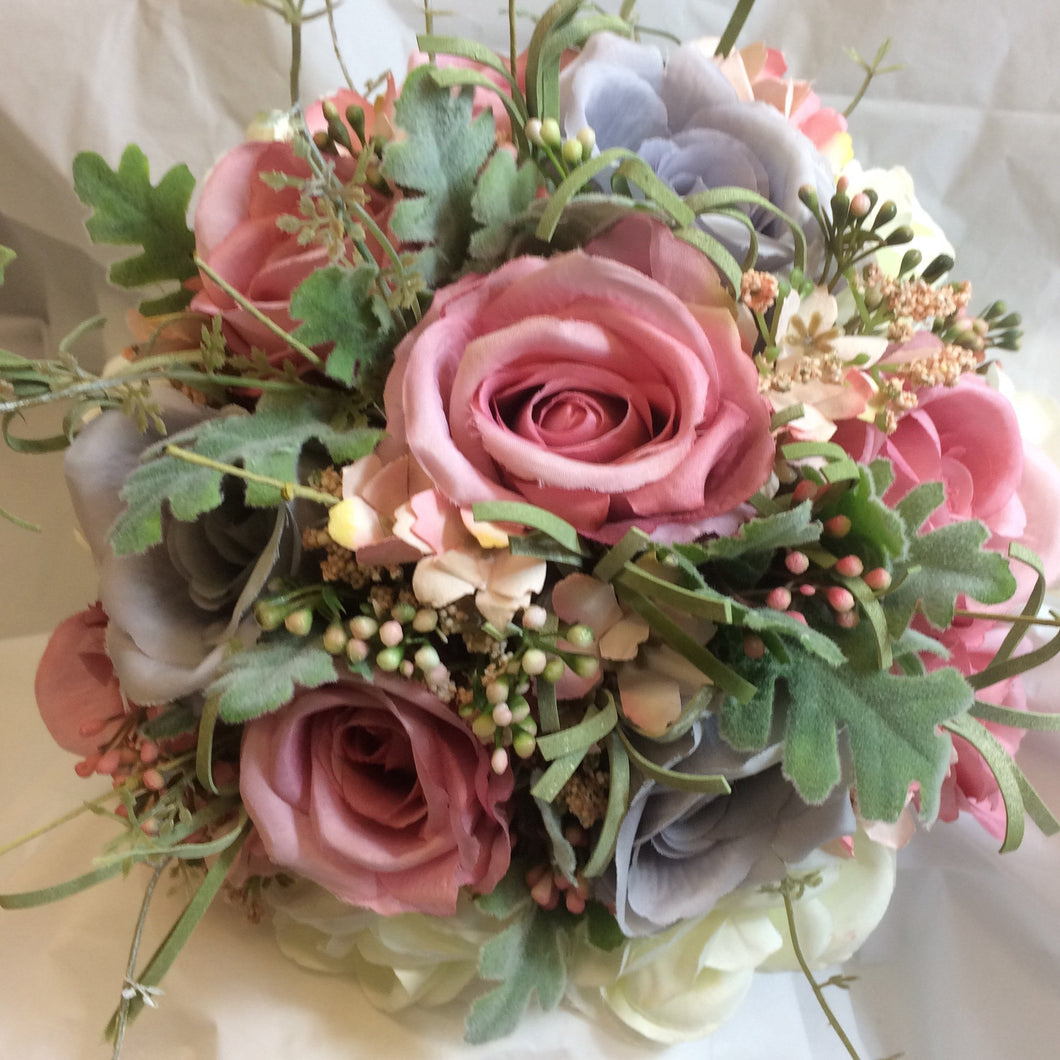 a brides bouquet of dusky pink, lavender/grey and ivory roses