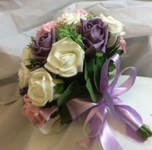 a wedding bouquet collection of pink and deep lilac roses