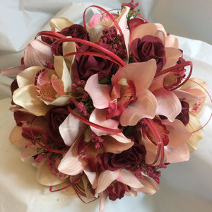 A brides bouquet of coral and burgundy artificial roses and orchids