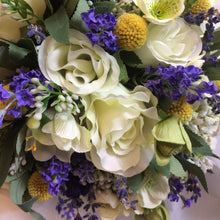 A brides bouquet using white ivory and blue flowers