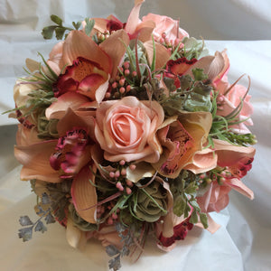 A brides bouquet of coral and grey artificial roses and orchids