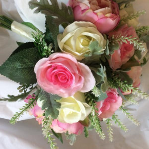 A brides bouquet of pink artificial silk rose flowers