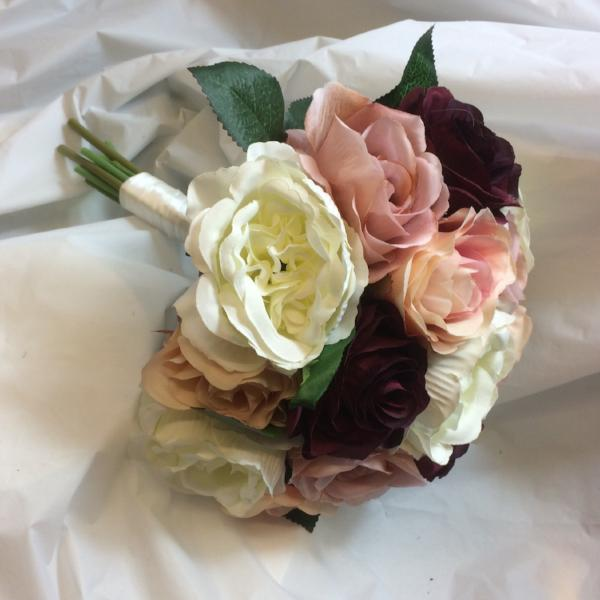 A bridal bouquet of silk roses in shades of burgundy & pink