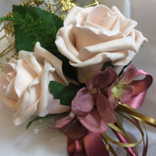 a bridesmaids gold metal heart shaped wand with mocha pink roses