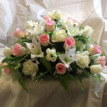 A top table flower arrangement of pink and ivory roses and lilies
