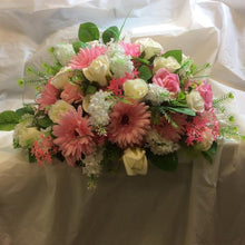 An artificial top table flower arrangement of pink and ivory roses and gerbera