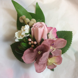An artificial corsage of pink roses and foliage