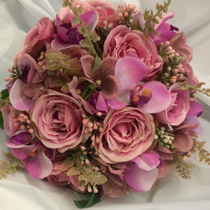 A brides bouquet of dusky pink roses, hydrangea and orchids