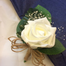 an artificial buttonhole featuring a single foam ivory rose