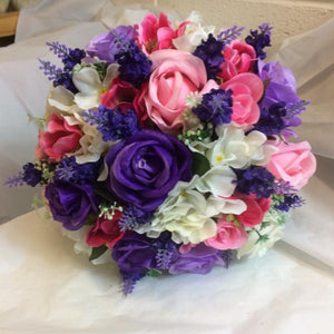 A brides wedding bouquet of artificial pink & purple flowers