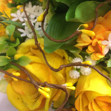 An artificial flower table centre in shades of yellow and white