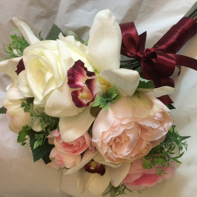 orchids peonies and roses feature in the bridal bouquet