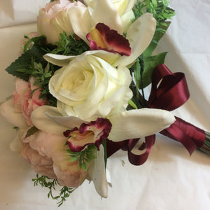 A brides hand-tied bouquet of artificial peonies roses and orchids