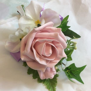 a corsage featuring vintage pink and lilac flowers