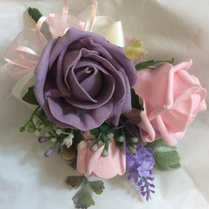 A Corsage featuring pale pink and lilac foam roses plus foliage