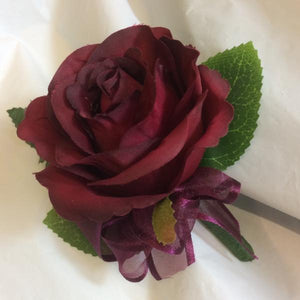 A buttonhole featuring a single burgundy silk rose