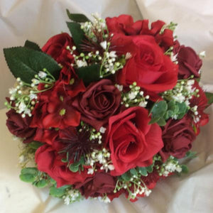 a wedding bouquet of red and burgundy artificial flowers