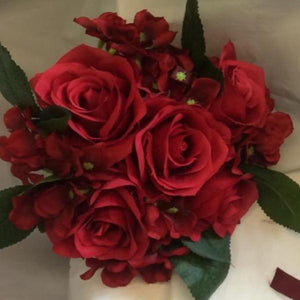 A bridesmaid bouquet or red artificial silk roses and hydrangea