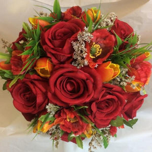 a bridal bouquet of red and orange roses and tulips