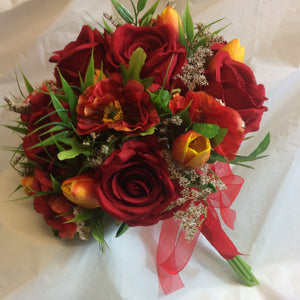 An artificial bridal bouquet of red roses and orange tulips