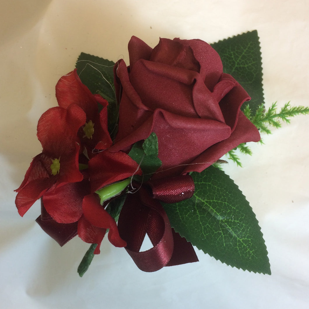 an artificial wedding buttonhole featuring a single burgundy foam rose