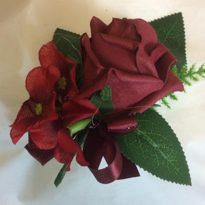 A buttonhole featuring a single burgundy foam rose & hydrangea