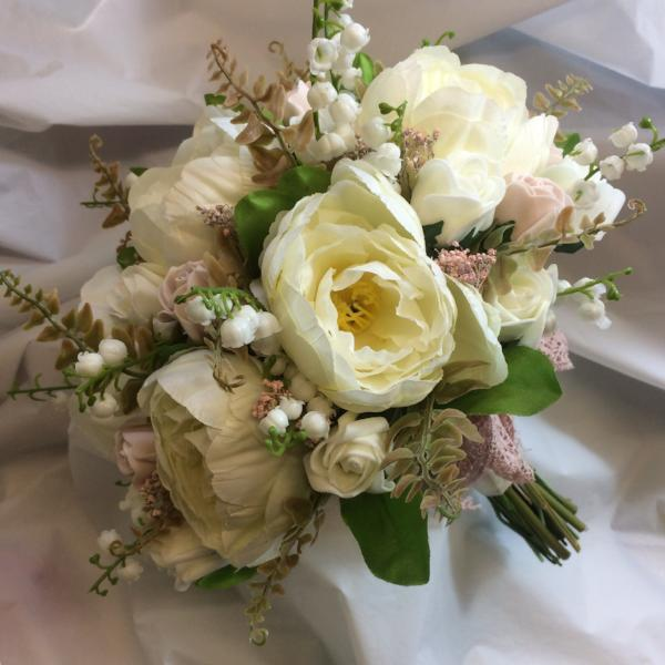 a wedding bouquet featuring dusky pink and ivory peonies roses and lily of the valley