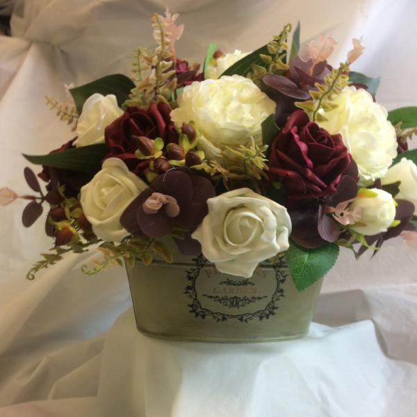An artificial flower arrangement in shades of ivory and burgundy